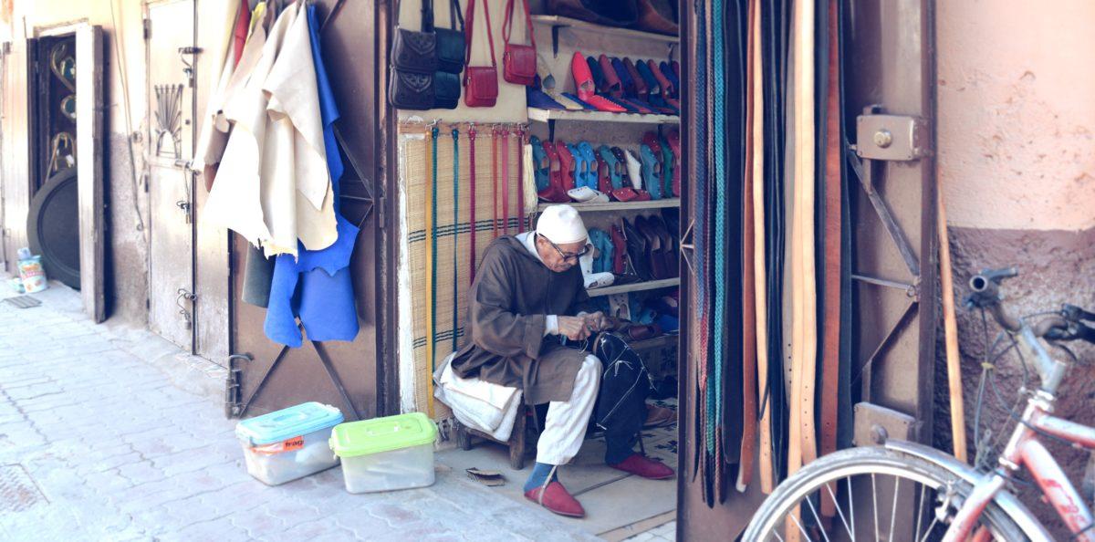 Mohamed coud devant sa boutique